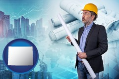 Wyoming - building contractor holding blueprints - cityscape background